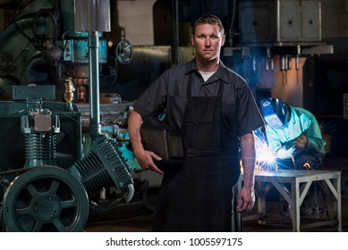 St Louis, Missouri, United States-circa 2015-Portrait of male welder with mask standing near compressor generator in dirty manufacturing factory plant with man welding in background, sparks flying.