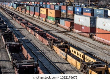 St. Louis, Missouri, United States-circa 2018-long line of train well cars and double stack freight container cars on railroad tracks in trainyard waiting for transport