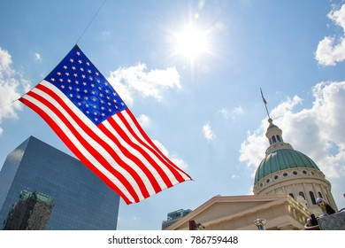 St Louis, Missouri, United States-circa 2014-Large American Flag Flying in Front of Old Courthouse and Modern Glass Buildings in Downtown St Louis Missouri During Forth of July Celebration VP Fair