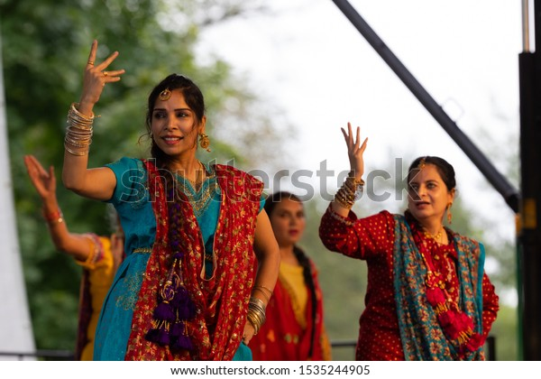 St. Louis, Missouri, USA - August 25, 2019: Festival of Nations, Tower Grove Park, Members of the Punjabi Bhangra Group, wearing traditional clothing, performing traditional dances from India
