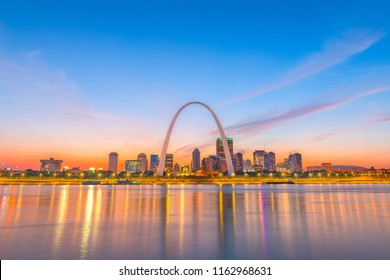 St. Louis, Missouri, USA downtown skyline and arch on the Mississippi River after sunset.
