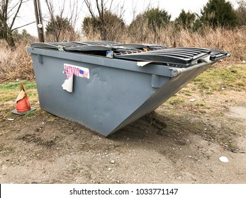St. Louis, Missouri, USA, February 23, 2018: Dumpster with a torn patriotic sticker partially torn off