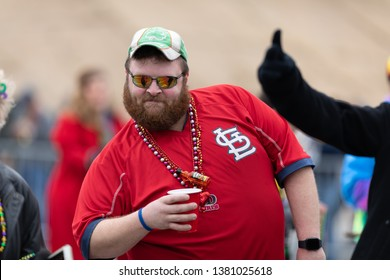 St. Louis, Missouri, USA - March 2, 2019: Bud Light Grand Parade, Man drinking and wearing a St Louis Cardinals shirt, posses for the camera during the parade
