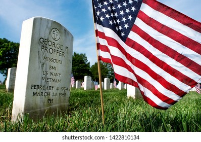 St. Louis, MO, USA, May 26, 2019 - Wide angle closeup of white military headstone at burial site with American flags and rows of headstones in background at military cemetery