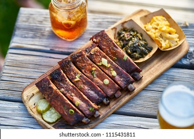 st louis style bbq ribs with collard greens and mac & cheese outside on picnic table during sunny summer day