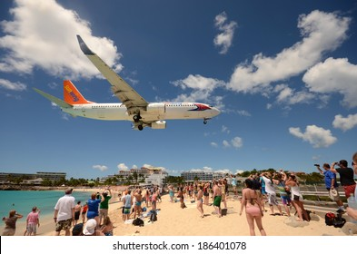 ST MAARTEN - MARCH 27: Beach crowds observe low flying airplanes landing near Maho Beach on the island of St Maarten in the Caribbean on March 27, 2014. it a favorite place to visit on the island
