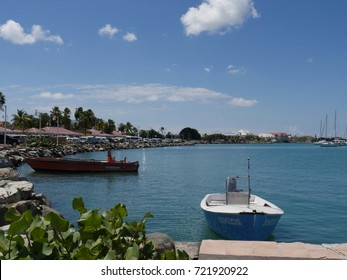ST. MAARTEN, WEST INDIES—Two small boats cocked along the rocky border of the Marigot Bay harbor in St. Maarten French side, West Indies on a beautiful sunny day in March 2017.