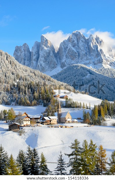 St. Magdalena or Santa Maddalena with its characteristic church in front of the Geisler, Odle, dolomites mountain peaks in the Val di Funes (Villnosstal) in South Tyrol in Italy in winter.