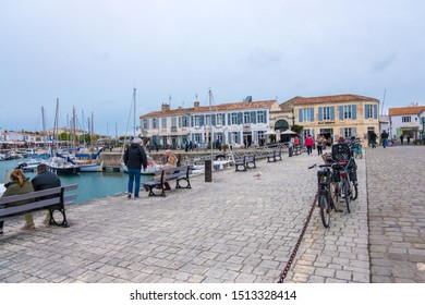 St Martin De Re, France - May 09, 2019: People relax on the picturesque promenade of the old harbor in Saint Martin de Re on Ile de Re island, France