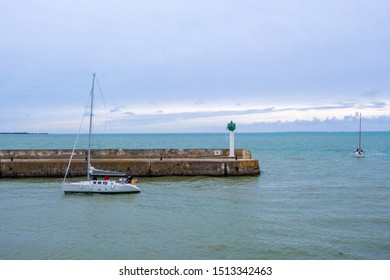 St Martin De Re, France - May 09, 2019: Sailboat passing the entrance of a Port de Saint-Martin-de-Re on the Ile de Re island in France