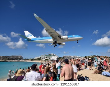 St Martin, Dutch Antelles - December 25, 2018: KLM heavy jet lands low over Maho Beach, St martin. The destination is a major tourist attraction of the island.