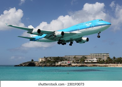 ST. MARTIN, NETHERLANDS ANTILLES - FEBRUARY 9: A KLM Boeing 747 approaching on February 9, 2014 in St. Martin. St. Martin is rated one of the most dangerous airports in the world.