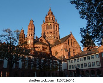 "St. Martin's Cathedral in Mainz, Germany (officially ""Der Hohe Dom zu Mainz"") in beautiful evening sunlight behind some smaller houses and trees and in front of clear blue sky"
