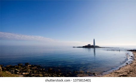 St Mary's Lighthouse and island lie north of the River Tyne and Whitley Bay on the North Sea coast of England. The blue sky and calm sea almost merge into one another on a warm spring morning.