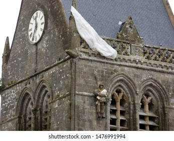 St Mere Eglise , FRANCE - AUGUST 7, 2019:  US Paratrooper dummy hanging from church tower to remember 82nd division airborne operations beginning of D-Day landings in Normandy, France in World War II