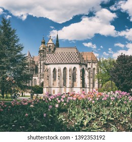 St. Michael chapel and St. Elisabeth cathedral in Kosice, Slovakia (Slovensko). Beautiful daytime cityscape in sunlight with flowers and blue sky with clouds