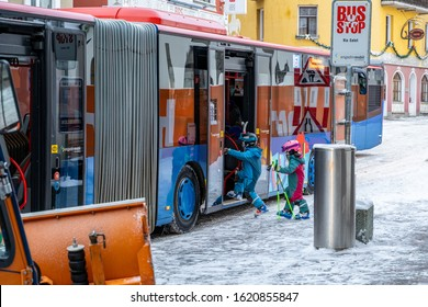St. Moritz, Switzerland - 22 December 2019 - Two young children skiers in their ski wear get on the bus to go skiing in St. Moritz, Switzerland on December 22, 2019