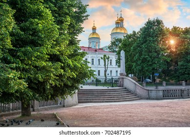 St. Nicholas Cathedral on the Kryukov Canal in St. Petersburg in the early summer morning and many pigeons under the tree