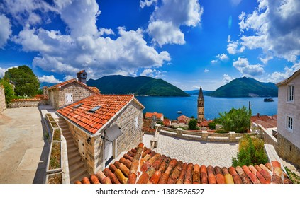 St. Nicholas church bell tower in Perast, old town on the Kotor Bay coast, Montenegro, Sveti Dorde isle on background. Scenic panorama view of the historic town of Perast