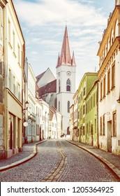 St. Nicholas' church with street, Znojmo, southern Moravia, Czech republic. Religious architecture. Travel destination. Yellow photo filter.