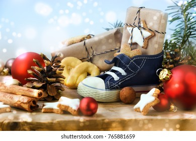St. Nicholas Day, Children's shoe with sweets, gifts and christmas ornaments on rustic wood, light blue snowy background, in Germany called Nikolaus, selected soft focus