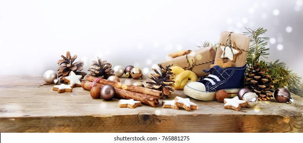 St. Nicholas Day, german Nikolaus, wide panoramic format with kid shoe, sweets and gifts  on rustic wood, background with copy space and blurry lights fades to white, selected focus