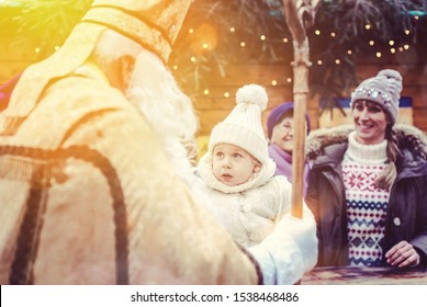St Nicholas and an extended family with child on the Christmas market