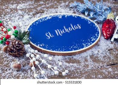 St. Nicholas Written In Chalk On Blue Chalkboard Holiday Sign Background With Snow And Decorations.
