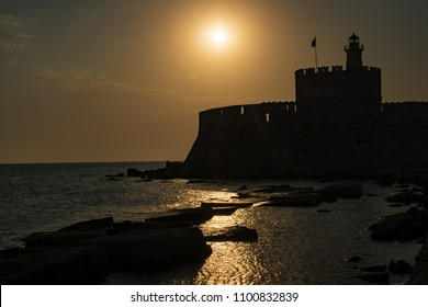 St. Nicoaus fortress with lighthouse in Mandraki harbor in City of Rhodes, sunset (Rhodes, Greece)