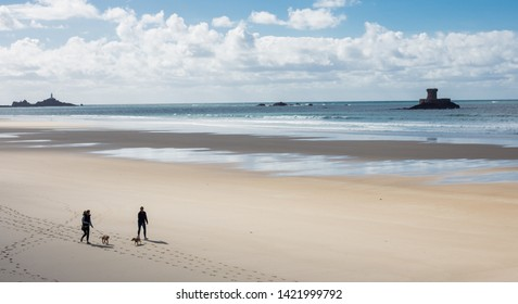 St. Ouens bay, Jersey, Channel Island 10/05/2018 : Two people walking their dogs on the shore, in a low tide sunny day.