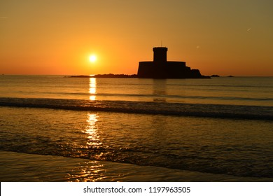 St Ouen's Bay, Jersey, U.K. An Autumn sunset with a 19th century military tower from the Napoleonic Wars surrounded by a calm sea.