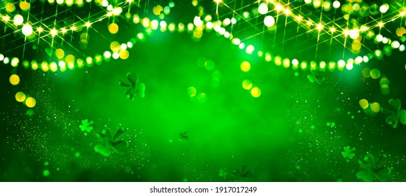 St. Patrick's Day abstract green background decorated with shamrock leaves. Patrick Day pub party celebrating. Abstract Border art design magic backdrop. Widescreen clovers on black with copy space - Shutterstock ID 1917017249