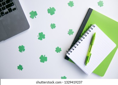 St Patrick's Day Background with Blank Notepad, Clovers, and Green Pen for Marketing, Business or School