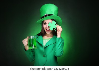 St. Patrick's Day. Beautiful woman wearing green hat with beer and paper clover