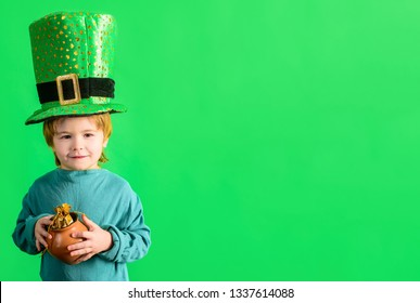 St. Patrick's day celebrations. Traditions of Saint Patrick Day. Cute boy holds pot of gold. Little boy with Leprechaun hat. Coin. Money. Kid in green costume and leprechaun top hat with golden buckle