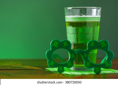 St. Patricks Day cold, frosty glass of green beer on a rustic wood background