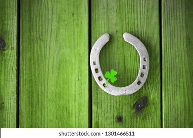 st patrick's day concept - horseshoe with shamrock on green wood boards