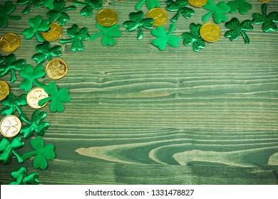 St Patricks Day corner border of shamrocks and gold coins on green wood background