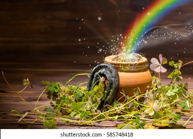 St Patricks day decoration with magic light rainbow pot full gold coins, horseshoe and shamrocks on vintage wooden background, close up