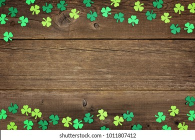 St Patricks Day double border of paper shamrocks over an old rustic wood background