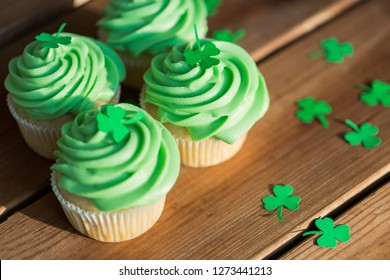 st patrick's day, food and holidays concept - close up of green cupcakes and shamrock on wooden table
