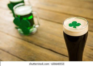 St Patricks Day glass of beer with shamrock on wooden surface
