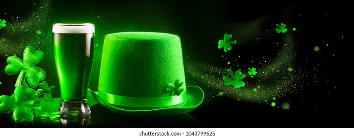 St. Patrick's Day Green Beer pint and leprechaun hat over dark background, decorated with shamrock leaves. Patrick Day pub party, celebrating. Glass of Green beer. Border art design Wide format banner