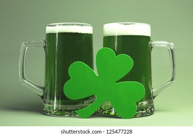 St Patrick's Day green beers with shamrock against green background.