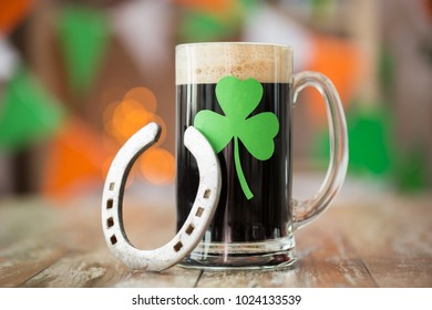 st patricks day, holidays and celebration concept - shamrock on glass of dark draft beer and horseshoe on wooden table