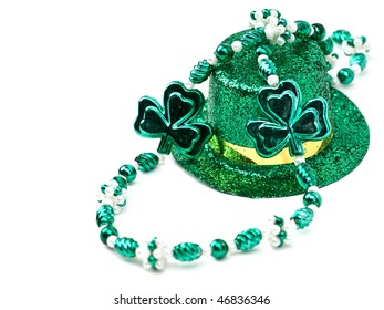 St. Patrick's Day inspired still-life of a glittering top hat and beads on white