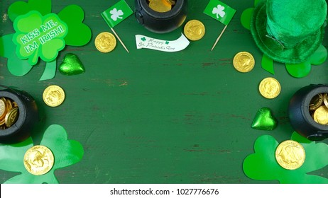 St Patrick's Day leprechaun hat with decorations on green rustic wood table background overhead