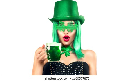 St. Patrick's Day leprechaun model girl in green hat and costume, holding mug of Green Beer pint over white background, surprised emotion. Patrick Day pub party, celebrating. Glass of Green beer