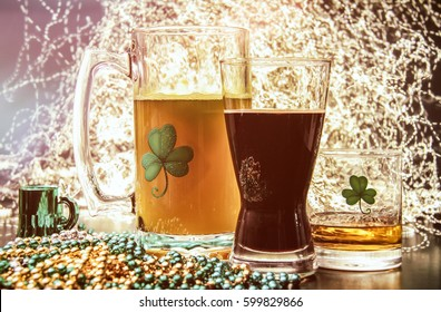 St Patricks Day Pub Alcohol. Saint Patrick's Day pub items, including a large mug of beer, a glass of Irish stout, and a shot of Irish Whiskey neat. Set against a celebration lit background.