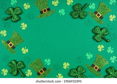 St Patricks Day shamrock and leprechaun hat frame. Above view over a green paper background with copy space.